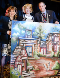Jacinthe Dubé, centre, Broker with Royal LePage Jacinthe Dubé Real Estate is pictured with her auction purchase, a painting that raised $7,000 in support of the Royal LePage Shelter Foundation. She is flanked by Johanne Robert, Manager, Network Services, Quebec Region and Dominic St-Pierre, Director, Quebec Region at the Royal LePage 100th Anniversary Kickoff in Montreal on Sept. 26.