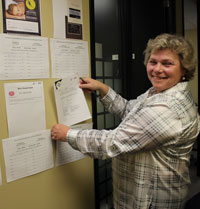 Royal LePage Performance Realty Sales Representative and Event Chairperson Jutta Witteveen displaying some of the dozens of silent auction items that were posted on the walls throughout the office.