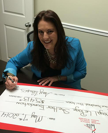 Amy Flowers of Royal LePage Meadowtowne Realty is pictured penning her cheque for $5,400 raised for the Shelter Foundation.
