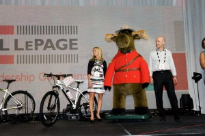"""Broker-owner JoAnn Jusdanis along with broker-manager Rob Landry of Royal LePage Burloak Real Estate Services prepare to hand over """"Royal LeMoose"""" to this year's highest bidders."""