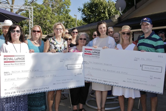 Hamilton, June 22, 2016 Rebecca Ryder (people immediately behind the cheque, L-R), Brenda Macdonald, Janice Hamilton of Halton Women's Place, Angie Mackie, Gloria Vidovich of Carpenter Hospice, JoAnn Landry and Rob Landry, all of Royal LePage Burloak, pose for a photo during the cheque presentation at the Royal LePage Burloak's annual BBQ. The Royal LePage Burloak Team donated money to the Halton Women's Place and the Carpenter Hospice. Photo by Noah Park, special to Metroland Media Group.