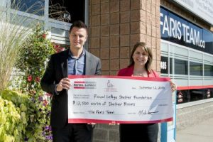 Broker Mark Faris presents a cheque for the purchase of 25,000 'Shelter Blooms' to Royal LePage Shelter Foundation fundraising and communications coordinator, Carly Neill